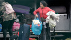 Migranten packen ihr Gepäck zusammen, um das Flüchtlinszentrum in Castelnuovo in Italien zu verlassen.