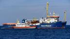 Ein Boot der Küstenwache nähert sich dem Rettungsboot Sea Watch.