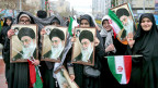 Iranische Frauen halten Porträts des obersten iranischen Führers Ayatollah Khamenei.