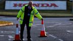 Ein Mann schließt den Eingang der Honda-Autofabrik in Swindon, England.