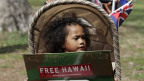 Ein kleines Mädchen mit einem Schild in der Hand, auf dem steht «Free Hawaii».