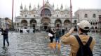 Touristen posieren für Fotos auf dem überfluteten Markusplatz in Venedig.