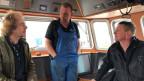 Der 38jährige Robin Bouma (Mitte) ist Crevettenfischer. Von Sonntagnacht bis Freitagmorgen ist er mit seiner Crew auf der Nordsee unterwegs. Im Steuerhaus, wo es angenehm warm ist, tauscht der Kutter-Besitzer die letzten Neuigkeiten mit zwei Kollegen aus.