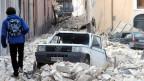Ein Mann geht am 9. April 2009 - drei Tage nach dem Erdbeben - in L'Aquila durch Trümmer.