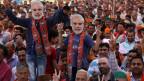 Inder, die Masken von Narendra Modi tragen, während des Wahlkampfs der Bharatiya Janata-Partei (BJP).