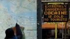 Tourist vor Stadtkarte von Amsterdam im Hintergrund ein Plakat der Gesundheitsbehörden, das vor den Gefahren harter Drogen warnt.