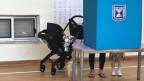 Eine israelische Stimmbürgerin zeigt ihrer Tochter, wie man in einem Wahllokal abstimmt.