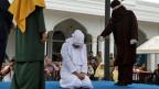 Eine Frau, die wegen sexueller Beziehungen außerhalb der Ehe gegen das Gesetz der Scharia verstossen hat, wird in Banda Aceh, Indonesien, öffentlich ausgepeitscht.