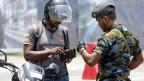 Srilankischer Sicherheitsbeamter prüft in Colombo den Identitätsnachweis eines Mannes.
