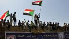 Demonstration in Khartoum mit einer sudanesischen Nationalflagge.
