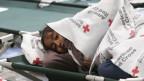 Ein junges Mädchen hält sich unter ihrer Decke warm in einer Flüchtlingsunterkunft in El Paso.