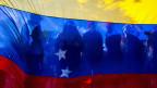 Anhänger von Juan Guaido vor der venezolanischen Flagge.