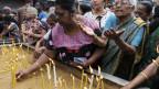 Nach den Anschlägen in Sri Lanka entzünden Passanten Kerzen für die Opfer.