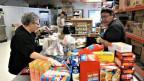 Helferinnen füllen kleine Plastikbeutel mit Essensrationen für die Migranten ab.