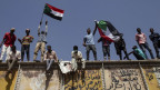 Sudanesische Demonstranten schwenken Nationalflaggen vor dem Militärhauptquartier in Khartum, Sudan.