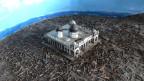 Man sieht zerstörte Holzhütten rund um eine Moschee.