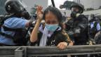 Eine Demonstrantin wird von der Bereitschaftspolizei angegriffen. Die Polizei in Hongkong hat Tränengas und Wasserwerfer gegen Tausende von Demonstranten eingesetzt, die sich gegen ein äußerst umstrittenes Auslieferungsgesetz aussprachen.