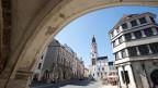Blick durch einen Torbogen über den Untermarkt auf den Rathausturm von Görlitz.