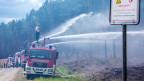 Feuerwehrleute löschen in der Nähe der evakuierten Ortschaft Alt Jabel einen grossflächigen Waldbrand.