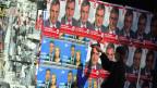 Ein Mann tapeziert eine Mauer mit Wahlplakaten.