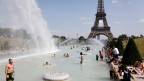 Menschen kühlen sich in den Trocadero-Brunnen gegenüber dem Eiffelturm in Paris ab.