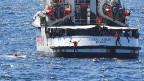 Migranten springen vom spanischen Rettungsschiff «Open Arms» nahe der italienischen Küste in Lampedusa, Italien, 20. August 2019.