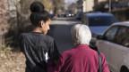 Eine Pflegerin geht mit einer Klientin spazieren.