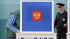 Eine Person gibt in Moskau ihre Stimme ab, beobachtet von einem Polizisten
