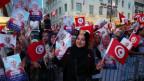 Das Bild zeigt eine Frau mit Kopftuch mit einer kleinen tunesischen Flagge in der Hand.