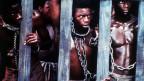 Symbolbild. Afrikanische Sklaven hinter Gittern.