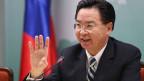 Zu sehen ist Taiwans Aussenminister Joseph Wu mit einer ausgestreckten Hand an einer Pressekonferenz.