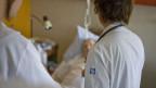 Visite von Ärzten an einem Spitalbett.