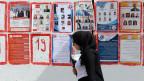 Eine Tunesierin geht an Listenplakaten für die bevorstehenden Parlamentswahlen in Tunis, Tunesien, 26. September 2019, vorbei.