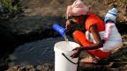 Frau mit Baby schöpft in Mabvuku, einem dicht besiedelten Vorort von Harare, Simbabwe, Wasser.