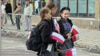 Pfadfinderinnen verteilen vor der Rede des Präsidenten in Wlodawa Polen-Fähnchen.