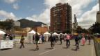 Zu sehen ist eine Strasse in der kolumbianischen Hauptstadt Bogota, auf der nur Fahrräder und Skateboards unterwegs sind. Es stehen weisse Verpflegungszelte.