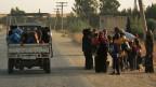 Syrer und Syrerinnen fliehen in Ras al Ayn im Nordosten Syriens vor türkischen Truppen.