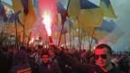 Das Bild zeigt Demonstranten, die ukrainische Flaggen und Leuchtfackeln halten.