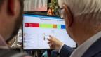 Zwei Personen verfolgen die Wahlergebnisse in Genf am 20. Oktober 2019.