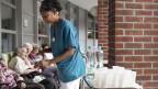 Eine Pflegefachfrau verteilt Wasser an die Bewohner und Bewohnerinnen eines Alterszentrums.