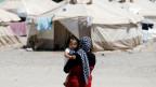 Eine Migrantin trägt ein Kind im Flüchtlingslager in Schisto bei Athen.