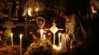 Zwei Männer sitzen am mit Kerzen und Blumen geschmückten Grab und gedenken den Verstorbenen.
