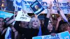 Zu sehen sind einige weibliche Demonstrantinnen, welche Bilder von Israels Premierminister Benjamin Netanjahu in die Höhe halten.