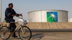 Ein Mitarbeiter fährt mit dem Fahrrad neben Öltanks in der Ölfabrik Saudi Aramco in Abqaiq, Saudi-Arabien.