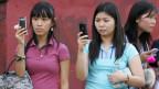 Frauen in Manila überweisen Geld auf dem Handy.
