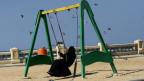 Ein verschleierte Frau auf einer Schaukel in Jiddah, Saudiarabien.
