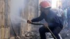 Ein Feuerwehrmann spritzt Wasser an der Stelle einer Autobombenexplosion vor einer Kirche in Qamischli, Afghanistan Syrien, 11. Juli 2019.