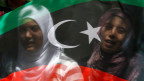 Lybien-Fahne, auf welcher sich Gesichter von zwei Frauen spiegeln.