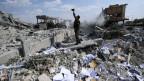 Ein syrischer Soldat filmt eine total zerbombte Siedlung.