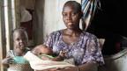 Nunu Tot sitzt mit ihrer frischgeborenen Tochter vor dem Zelt. Das Mädchen heisst Nyamal - übersetzt «Frieden».